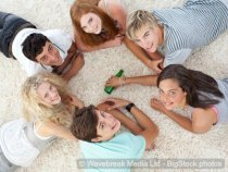 Young group of girls and guys playing spin the bottle
