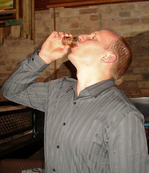 Man drinking a shot of alcohol while playing the Never Have I Ever game