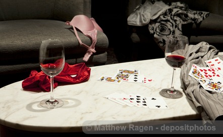 Stripped clothes with alcohol drinks and playing cards