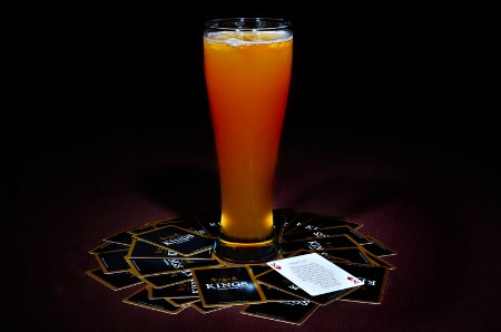 A glass full of beer placed over the king cards