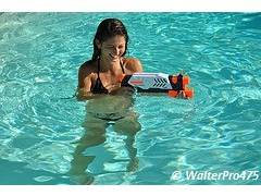 Girl playing with water-gun in a pool