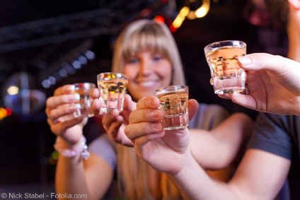 Blonde women doing cheers with shots