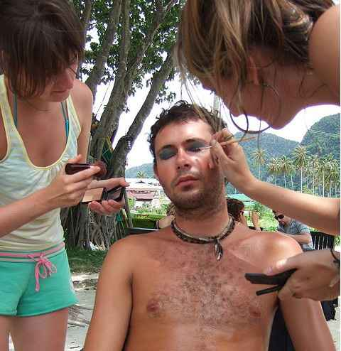 Two girls putting on make up on a topless man