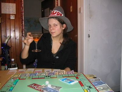 Girl drinking while playing the Monopoly game