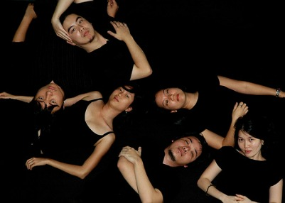 A group of girls and guys lying and posing in black dresses