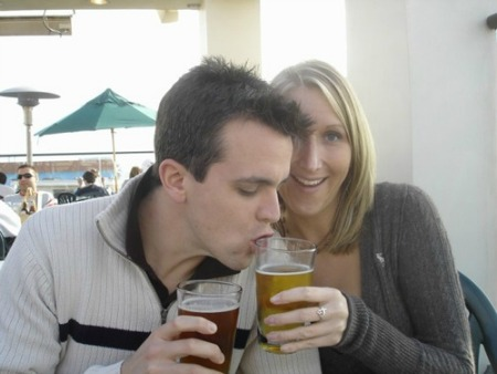 A young guy drinking beer from a girl's glass