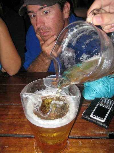 man watching at a large beer jug in a funny way