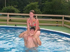 Swimming Pool Games A Girl is sitting on the guy's shoulders