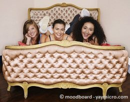 three girls lying on bed at a sleepover night