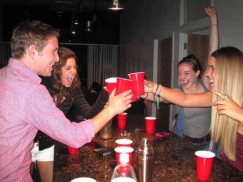 Three hot girls and a guy drinking at party