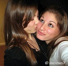 beautiful girl kissing on the cheek of other girl
