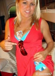 blonde girl pointing out an id card between her breasts
