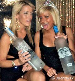 Sexy blondes holding large vodka bottles