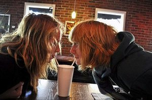 Two girls drinking from the same cup
