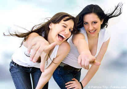 Two girls pointing and laughing
