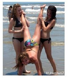 Bikini Girls holding another girl from legs helping her to do a handstand