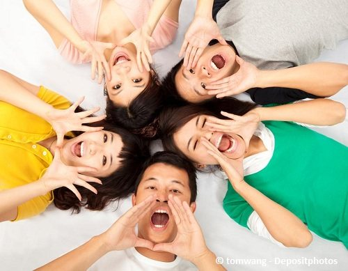 A group of teenage guys and girls shouting together