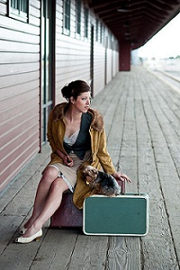 Lady with a green suitcase and a little puppy