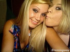 two blondes smiling and posing for a kiss