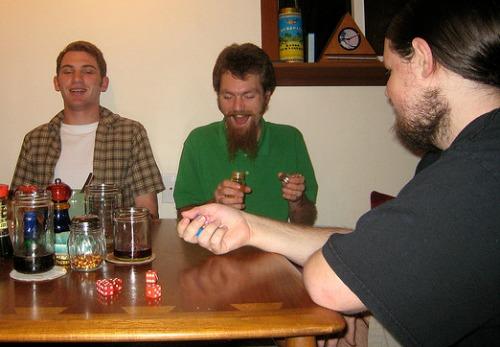 3 men playing drinking dice games