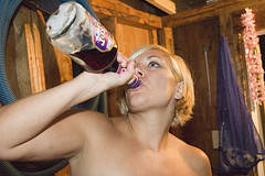 Topless girl drinking directly from the bottle